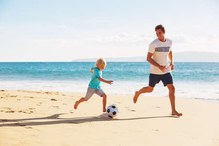 Photo pour Happy Father and Son Having Fun Playing Soccer on the Beach - image libre de droit