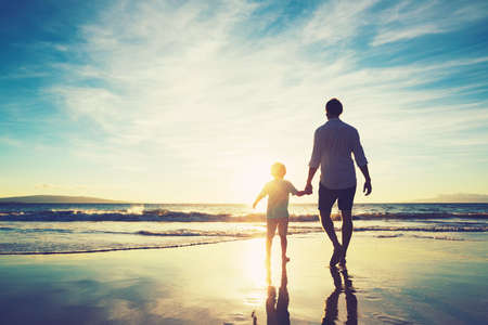 Foto de Father and Son Holding Hands Walking Together on the Beach at Sunset - Imagen libre de derechos