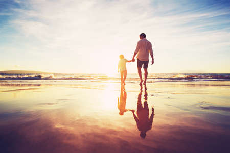Photo pour Father and Son Holding Hands Walking Together on the Beach at Sunset - image libre de droit