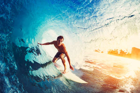 Foto de Surfer on Blue Ocean Wave Getting Barreled at Sunrise - Imagen libre de derechos