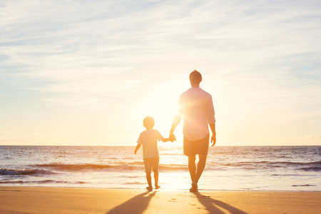 Photo pour Father and Son Walking Together on the Beach at Sunset. Fatherhood Family Concept - image libre de droit