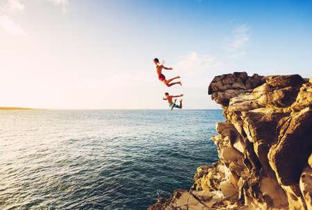 Photo pour Friends Cliff Jumping into the Ocean at Sunset, Outdoor Adventure Lifestyle - image libre de droit