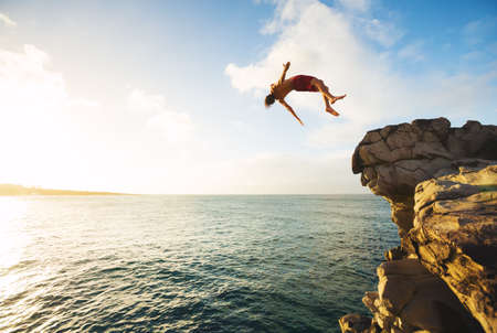 Foto de Cliff Jumping into the Ocean at Sunset, Outdoor Adventure Lifestyle - Imagen libre de derechos