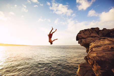 Photo pour Cliff Jumping into the Ocean at Sunset, Outdoor Adventure Lifestyle - image libre de droit