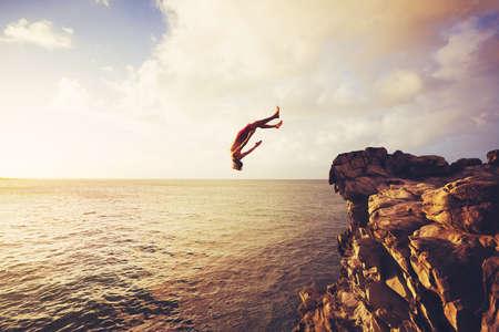Photo pour Cliff Jumping into the Ocean at Sunset, Summer Fun Lifestyle - image libre de droit