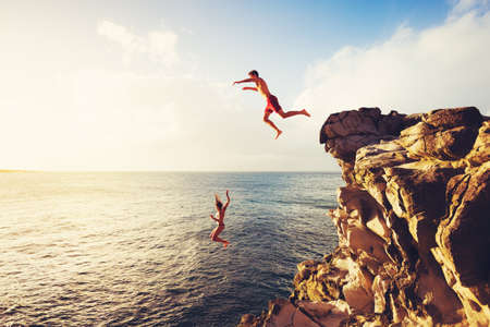 Photo pour Friends Cliff Jumping into the Ocean at Sunset, Outdoor Adventure Lifestyle - image libre de droit
