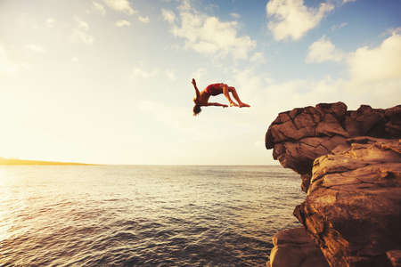 Photo pour Cliff Jumping into the Ocean at Sunset, Summer Fun Lifestyle - image libre de droit