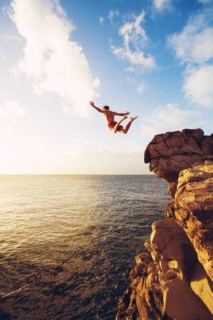Foto de Cliff Jumping into the Ocean at Sunset, Outdoor Adventure Lifestyle - Imagen libre de derechos