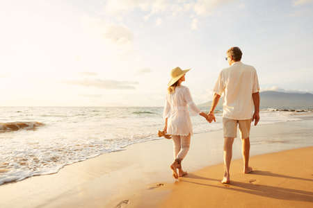 Foto de Happy Romantic Middle Aged Couple Enjoying Beautiful Sunset Walk on the Beach. Travel Vacation Retirement Lifestyle Concept - Imagen libre de derechos