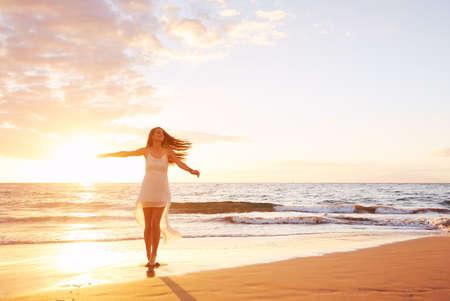 Photo pour Happy carefree woman dancing at sunset on the beach. Happy free lifestyle concept. - image libre de droit