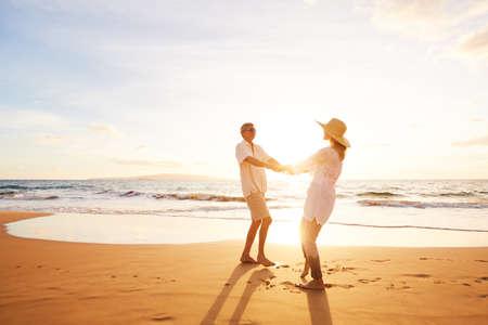 Foto de Happy Romantic Middle Aged Couple Enjoying Beautiful Sunset on the Beach. Travel Vacation Retirement Lifestyle Concept. - Imagen libre de derechos