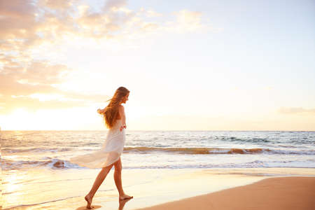 Photo pour Happy carefree woman dancing at sunset on the beach. Happy free lifestyle concept. - image libre de droit