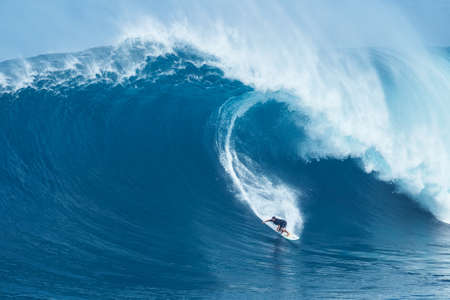 Photo pour MAUI, HI - JANUARY 16 2016: Professional surfer Joao Marco Maffini rides a giant wave at the legendary big wave surf break known as Jaws on one the largest swells of the year. - image libre de droit