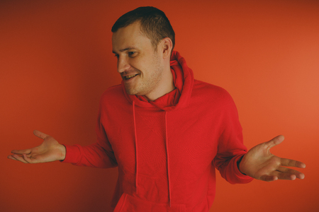 Foto per Crazy and charismatic guy posing on orange background. A man in a red tracksuit. - Immagine Royalty Free