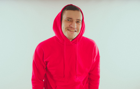Foto per Crazy and charismatic guy posing. A man in a red tracksuit. Man isolated on white background, space for text - Immagine Royalty Free