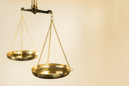 Photo pour Two bowls of scales made of golden metal suspended on chains on a beige background - image libre de droit