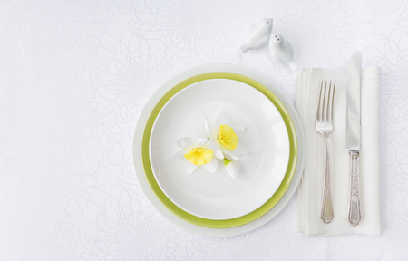Photo pour Classic serving for a gala dinner with luxurious porcelain, silverware and spring flowers on a white tablecloth, with copy-space - image libre de droit