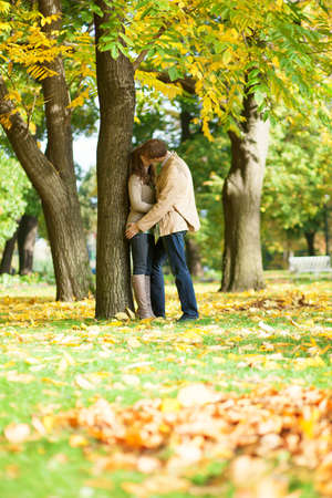 Photo for Couple kissing in park on a fall day - Royalty Free Image
