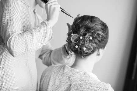 Foto de Young bride getting her hair done before wedding - Imagen libre de derechos