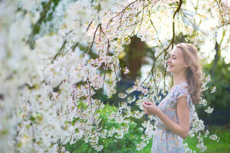 Photo for Beautiful young girl in cherry blossom garden on a spring day - Royalty Free Image
