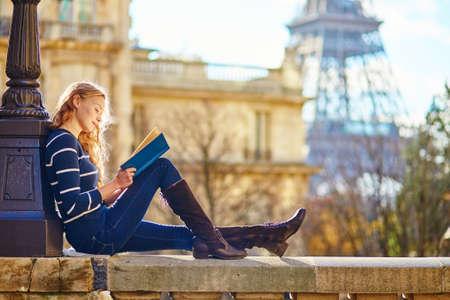 Foto de Beautiful young woman in Paris, reading a book - Imagen libre de derechos