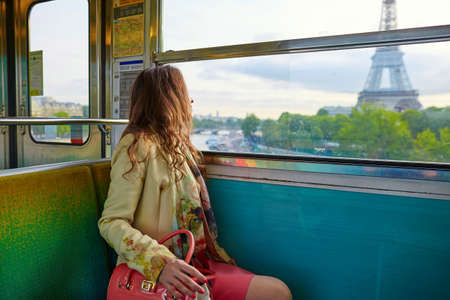 Photo pour Young beautiful Parisian woman travelling in a subway train, sitting near the window and looking at the Eiffel tower - image libre de droit