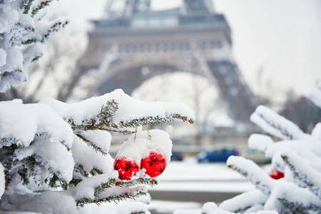 Photo pour Christmas tree decorated with red balls and covered with snow on a rare snowy day in Paris. Eiffel tower is in the background - image libre de droit