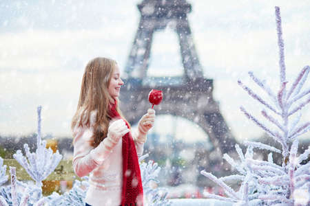 Foto de Girl with caramel apple on a Parisian Christmas market during snowfall near white snowy Christmas trees and with the Eiffel tower in the background - Imagen libre de derechos