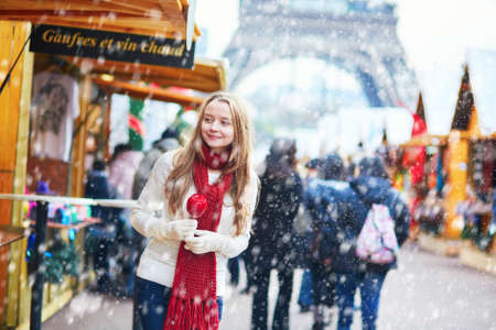 Photo pour Happy young girl with caramel apple on a Parisian Christmas market with the Eiffel tower in the background during snowfall - image libre de droit