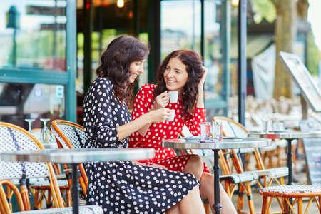 Foto de Beautiful twin sisters drinking coffee in a cozy outdoor cafe in Paris, France. Happy smiling girls enjoy their vacation in Europe - Imagen libre de derechos