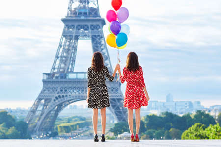 Foto de Beautiful twin sisters in red and black polka dot dresses with huge bunch of colorful balloons in front of the Eiffel tower in Paris, France - Imagen libre de derechos