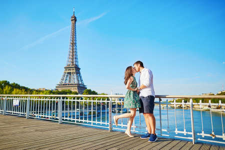 Photo pour Young romantic couple having a date and kissing near the Eiffel tower on a bridge over the Seine in Paris, France - image libre de droit