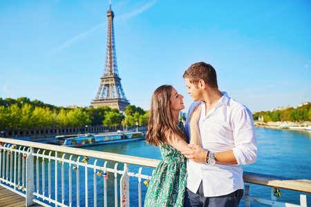 Photo pour Young romantic couple having a date near the Eiffel tower on a bridge over the Seine in Paris, France - image libre de droit