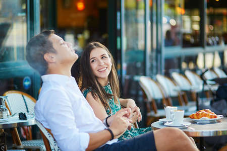 Foto de Young romantic couple drinking coffee, eating traditional French croissants and smoking in a cozy outdoor cafe in Paris, France - Imagen libre de derechos