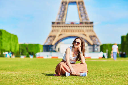Photo for Beautiful young tourist or student girl in Paris sitting on the grass near the Eiffel tower on a summer day - Royalty Free Image