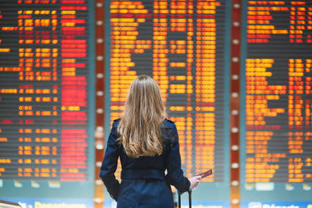 Foto de Young woman in international airport looking at the flight information board, holding passport in her hand, checking her flight - Imagen libre de derechos