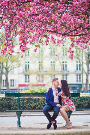 Photo pour Romantic couple having a date in Paris on a spring day with beautiful cherry blossoms in the background - image libre de droit