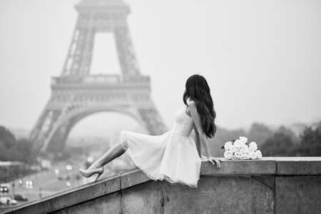 Photo pour Elegant Parisian woman in pink tutu dress with white roses sitting near the Eiffel tower at Trocadero view point in Paris, France, black and white image - image libre de droit