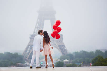 Photo for Beautiful romantic couple in love with bunch of red balloons together near the Eiffel tower in Paris on a cloudy and foggy rainy day - Royalty Free Image