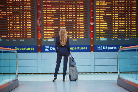Photo for Young elegant business woman with hand luggage in international airport terminal, looking at information board, checking her flight. Cabin crew member with suitcase. - Royalty Free Image