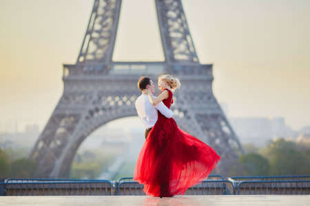 Photo pour Beautiful romantic couple dancing in front of the Eiffel tower in Paris, France - image libre de droit