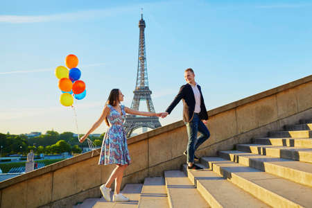Photo pour Romantic couple with colorful balloons near the Eiffel tower in Paris, France, walking up the stairs - image libre de droit