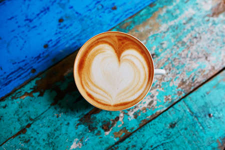 Photo pour Cup of fresh coffee with heart form milk drawing on blue wooden table, view from above, flat lay - image libre de droit