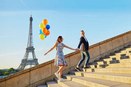 Photo pour Loving couple with bunch of colorful balloons walking up the stairs near the Eiffel tower in Paris, France - image libre de droit