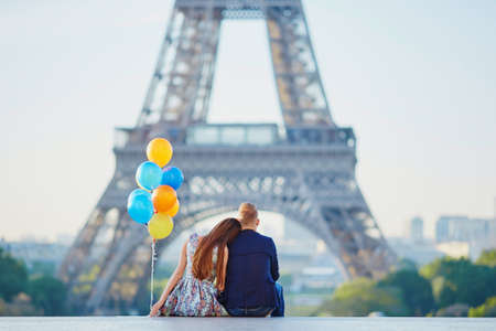 Photo pour Loving couple with bunch of colorful balloons looking at the Eiffel tower in Paris, France - image libre de droit