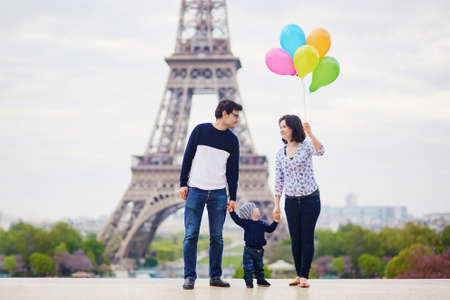 Photo pour Happy family of three with bunch of colorful balloons in Paris near the Eiffel tower. Mother, father and little son enjoying their vacation in France - image libre de droit