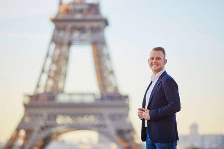 Photo pour Handsome young man near the Eiffel tower in Paris - image libre de droit