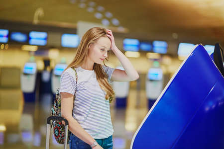 Photo pour Young tourist girl with backpack and carry on luggage in international airport, doing self check-in, looking upset and worried. Delayed or missed flight concept - image libre de droit