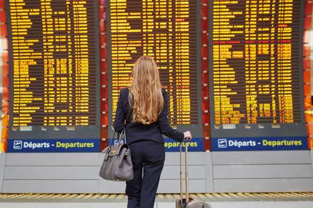 Photo pour Young elegant business woman with hand luggage in international airport terminal, looking at information board, checking her flight. Cabin crew member with suitcase - image libre de droit
