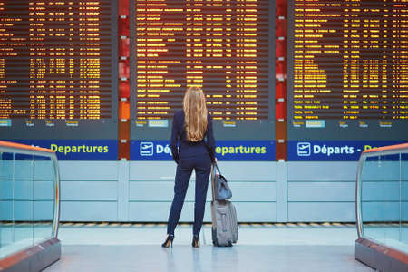 Foto de Young elegant business woman with hand luggage in international airport terminal, looking at information board, checking her flight. Cabin crew member with suitcase - Imagen libre de derechos